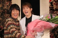 Wrestling star Saori Yoshida, right, smiles after receiving a bouquet from her mother Yukiyo at a news conference on her retirement at a hotel in Tokyo on Jan. 10, 2019. (Mainichi/Naoaki Hasegawa)