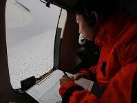 オホーツク海を南下する流氷を調べる観測員=北海道網走沖で2019年1月10日午前、第1管区海上保安本部の航空機から貝塚太一撮影