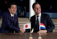 会談で握手する安倍首相(左)とルッテ首相=2019年1月9日、AP