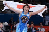 Saori Yoshida raises a Japanese flag to celebrate her third consecutive Olympic gold in the 55-kilogram division in women's wrestling, at the London Olympics on Aug. 9, 2012. (Mainichi/Masaru Nishimoto)