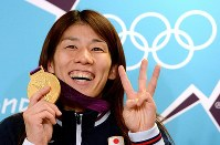 Saori Yoshida shows off her gold medal with three fingers raised, one for each Olympic championship she has won in the 55-kilogram division in women's wrestling, at the London Olympics on Aug. 10, 2012. (Mainichi/Ryoichi Mochizuki)
