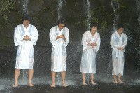 The Japanese women's wrestling team for the 2004 Athens Olympics, from left, Kyoko Hamaguchi, Kaoru Icho, Saori Yoshida and Chiharu Icho, meditate beneath the waterfall at Oiwasan Nissekiji temple in the town of Kamiichi, Toyama Prefecture, on July 3, 2004. (Mainichi/Takashi Fujiwara)