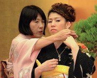 Saori Yoshida's mother Yukiyo Yoshida, left, fastens a golden pearl necklace commemorating her daughter's People's Honor Award around her neck, at the award ceremony at the prime minister's office on Nov. 7, 2012. (Mainichi/Taro Fujii)