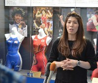Wrestler Saori Yoshida speaks in front of an exhibition of her Olympic uniforms at the