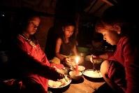 家と土地を失いろうそくの明かりを頼りにバラックの家で夕食を食べる子どもたち=カンボジア・プノンペンで2013年12月5日、フォトジャーナリストの高橋智史さん撮影