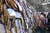 合格を願い、絵馬をかける女性=東京都文京区の湯島天神で2019年1月4日午後0時32分、藤井達也撮影