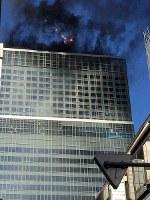 黒煙をあげて燃えるビル=東京都港区で2019年1月11日午後2時9分、読者提供
