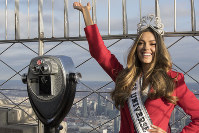 In this Nov. 28, 2017 file photo, Miss Universe 2017 Demi-Leigh Nel-Peters, of South Africa, poses for photographers on the 86th Floor Observation Deck of the Empire State Building in New York. (AP Photo/Mary Altaffer)