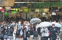 雪が舞うなか、街を歩く人たち=東京・JR新宿駅前で2019年1月12日午前11時37分、長谷川直亮撮影