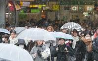 小雪が舞う中、街を歩く買い物客ら=JR新宿駅前で2019年1月12日午前11時37分、長谷川直亮撮影