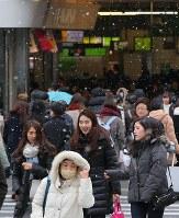 小雪が舞う中、街を歩く買い物客ら=JR新宿駅前で2019年1月12日午前11時35分、長谷川直亮撮影