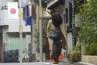 雪の降るなか、コートを着て歩く女性=東京都世田谷区で2019年1月12日午前11時26分、渡部直樹撮影