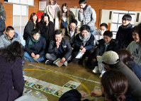 タイムカプセルの中身に笑顔を見せる大川海成さん(前列左から2人目)ら新成人=岩手県山田町の大沢小体育館で2019年1月12日午後、篠口純子撮影