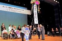 くす玉を割って成人式と還暦を祝う参加者ら=尼崎市昭和通2のあましんアルカイックホール・オクトで2019年1月13日、山田泰正撮影