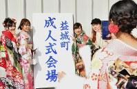 成人式会場の看板の前で記念撮影する新成人たち=熊本県益城町の「サクラリーナ」で2019年1月13日午前11時37分、清水晃平