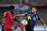 アジア杯【日本・オマーン】ボールを競り合う日本DF酒井=2018年1月13日UAE・アブダビのザイードスポーツシティスタジアムで、AP