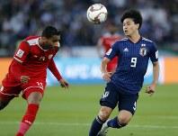 アジア杯【日本・オマーン】ボールを競り合う日本MF南野=2018年1月13日UAE・アブダビのザイードスポーツシティスタジアムで、AP