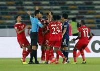 アジア杯【日本・オマーン】日本DF長友の体を張ったブロックに、オマーンの選手はハンドを主張し、いっせいに主審に駆け寄った=2018年1月13日UAE・アブダビのザイードスポーツシティスタジアムで、AP