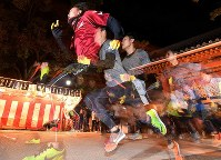 Runners sprint toward the main hall of Nishinomiya Shrine at the annual race to select the year's