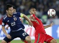 アジア杯【日本・オマーン】ボールを競り合う日本DF吉田=2018年1月13日UAE・アブダビのザイードスポーツシティスタジアムで、AP