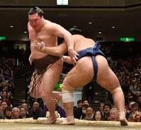 栃煌山に後ろに回り込まれた白鵬(左)。土俵に足をかけながら身をかわし、突き落としで勝った=東京・両国国技館で2019年1月14日、丸山博撮影