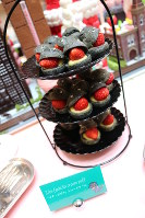 Cream puffs made to look like the newest Godzilla incarnation's face are arranged on a sweets tower at