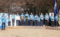 学生らの前で総合優勝を報告する両角速監督(左端)と選手たち