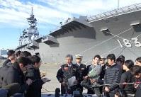 海上自衛隊最大の護衛艦「いずも」を背景に記者団の取材に応じる岩屋毅防衛相(中央)=神奈川県横須賀市の海自横須賀基地で昨年12月19日、木下訓明撮影