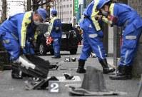 歩道にばらばらに散らばった車の部品と事故を起こした乗用車(奥)=東京都渋谷区で2019年1月16日午後2時39分、竹内紀臣撮影