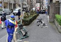 歩道にばらばらに散らばった車の部品と事故を起こした乗用車(右奥)=東京都渋谷区で2019年1月16日午後2時44分、竹内紀臣撮影