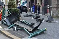 歩道にばらばらに散らばった車の部品と事故を起こした車両(奥)=東京都渋谷区で2019年1月16日午後2時34分、竹内紀臣撮影