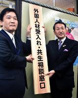 窓口の看板を設置する平井伸治鳥取県知事(右)ら=同県庁で、園部仁史撮影