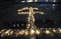 「生」の文字をかたどった石積みの前で黙とうする人たち=兵庫県宝塚市で2019年1月16日午後5時46分、久保玲撮影