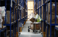Lovespace warehouse worker Pawel Mazur unloads boxes from a trolley to place them into their allocated zones at the warehouse in Dunstable, Britain, on Jan. 14, 2019. (AP Photo/Alastair Grant)
