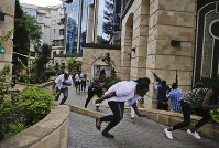 Civilians flee as security forces aim their weapons at the buildings of a hotel complex in Nairobi, Kenya, on Jan. 15, 2019. (AP Photo/Khalil Senosi)