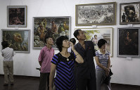 In this July 26, 2015 file photo, North Koreans look at paintings on display in Pyongyang, North Korea. (AP Photo/Wong Maye-E)
