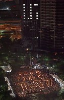 People offer a silent prayer to the victims of the 1995 Great Hanshin Earthquake with an image of