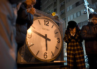 People offer a silent prayer to the victims of the 1995 Great Hanshin Earthquake in front of a monument to show a clock which stopped at the time of the jolt in the city of Nishinomiya, Hyogo Prefecture, in western Japan, in the predawn hours of Jan. 17, 2019. (Mainichi/Rei Kubo)