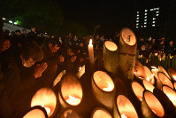 People offer a silent prayer to the victims of the 1995 Great Hanshin Earthquake with bamboo lanterns at an annual memorial event at Higashi Yuenchi Park in Kobe's Chuo Ward, in western Japan, at the time of the jolt, 5:46 a.m. of Jan. 17, 2019. (Mainichi/Naohiro Yamada)