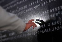 A man touches a stone monument, on which names of the victims of the 1995 Great Hanshin Earthquake were engraved, at a memorial park in the city of Nishinomiya, Hyogo Prefecture, in western Japan, in the predawn hours of Jan. 17, 2019. (Mainichi/Rei Kubo)
