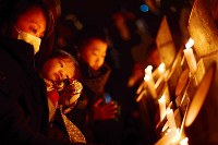 Hiromi Tanaka, 37, and her 9-month-old daughter Sakura stare into bamboo lanterns as the mother prays for the victims of the 1995 Great Hanshin Earthquake, including her relative, at Higashi Yuenchi Park in Kobe's Chuo Ward, in western Japan, in the predawn hours of Jan. 17, 2019. (Mainichi/Naohiro Yamada)
