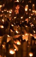 竹灯籠(とうろう)に手を合わせる女性=神戸市中央区の東遊園地で2019年1月17日午後7時39分、平川義之撮影
