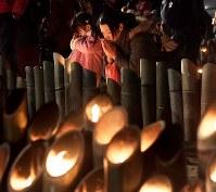 竹灯籠(とうろう)に手を合わせる松本恵美さん(42)と長女心春ちゃん(2)。2人とも初めて「追悼のつどい」を訪れた。恵美さんは震災当時、神戸市内で被災し、いろいろな人に助けられたと振り返る。「地震などの災害に心春が遭った時、誰かを助けられる気持ちを持つことを忘れないでね」と心春ちゃんに伝えた=神戸市中央区の東遊園地で2019年1月17日午後5時59分、平川義之撮影