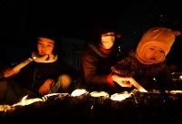 「1・17KOBEに灯りを in ながた」で、5歳と3歳の娘とともに参加した神戸市長田区の安達久美さん(中央)。安達さんは長女と同じ歳で震災を体験した。「子どもたちには命を大切にし、助け合う心を持ってほしい」と話した=神戸市長田区で2019年1月17日午後5時55分、山田尚弘撮影