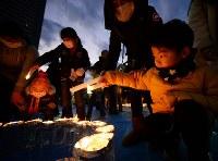 「1・17KOBEに灯りを in ながた」で、ろうそくに明かりをともす人たち=神戸市長田区で2019年1月17日午後5時31分、山田尚弘撮影