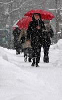 今季一番の冷え込みとなった札幌市で降りしきる雪の中を歩く人たち=同市中央区で2019年1月17日午後2時半、竹内幹撮影