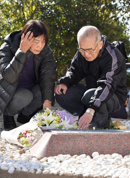 長男の信宏さんが生前着けていた腕時計をして、神戸大学犠牲者慰霊碑の銘板を触る藤原宏美さん(右)と妻美佐子さん=神戸市灘区で2019年1月17日午前11時55分、山崎一輝撮影