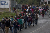 Honduran migrants walk along the roadside through Esquipulas, Guatemala, as they make their way toward the U.S. border, early on Jan. 16, 2019. (AP Photo/Moises Castillo)