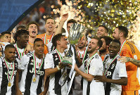 Juventus' Paulo Dybala, center left, and Juventus' Miralem Pjanic raise the trophy at the end of the Italian Super Cup final soccer match between AC Milan and Juventus at King Abdullah stadium in Jiddah, Saudi Arabia, on Jan. 16, 2019. (AP Photo)