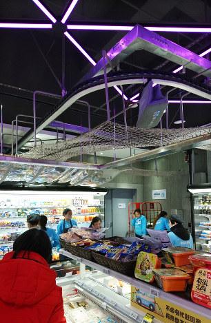 オンラインの注文に応じて店員が詰めた専用バッグは、天井を走るレールでバックヤードの配送スタッフに届けられる(上海市のフーマーで2018年12月)